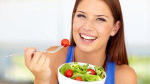 Beautiful young woman enjoying a healthy green salad